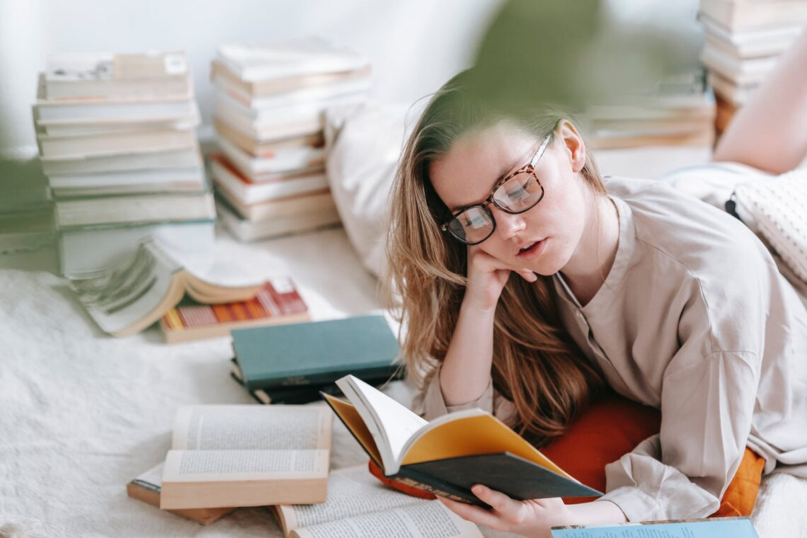 pensive woman reading book on plaid