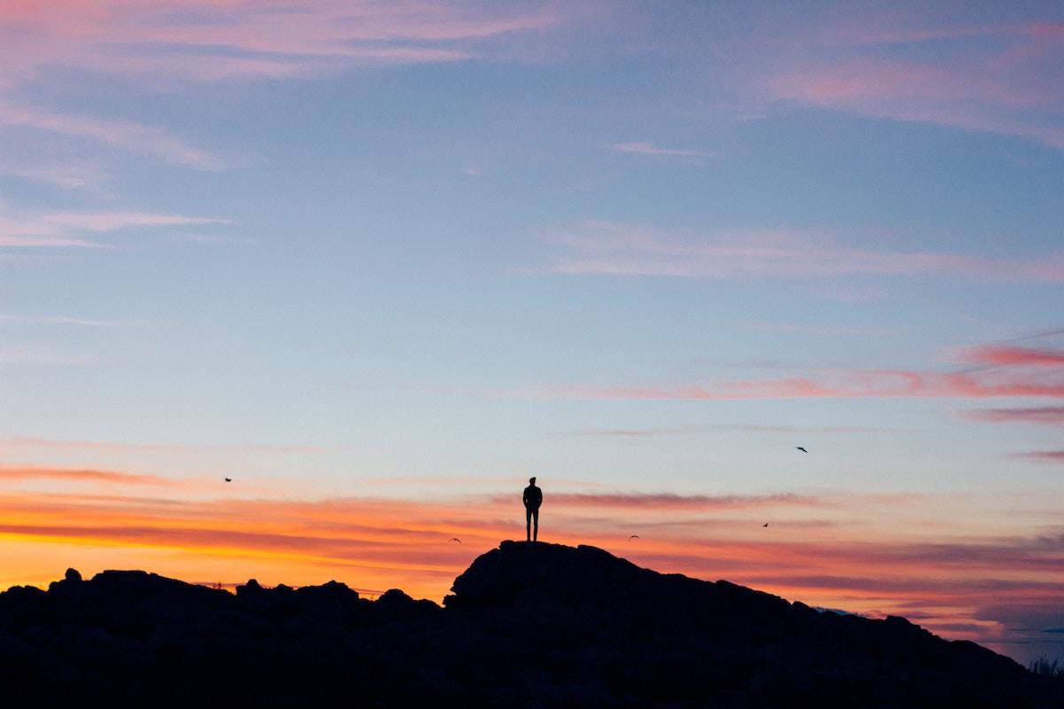 Man alone on mountain at sunset
