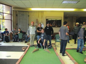 Corey Runyan, Kevin Sergeff, Michael Sammarco and Dylan Marketich pose with their miniature golf course in Moser Hall. Photo courtesy of Kerry Meyers.