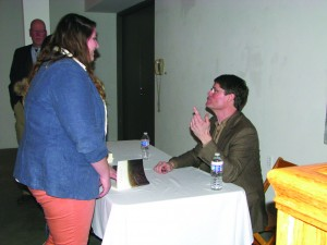 Bruce Mills explains to aYSU studentthe dynamics behind his memoir as he signs her book.