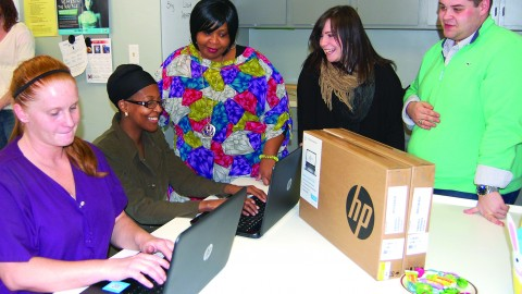 Enactus members with the newly donated laptops. The computers will help connect women at the Beatitude House with education and employment opportunities. Photo courtesy of Enactus.