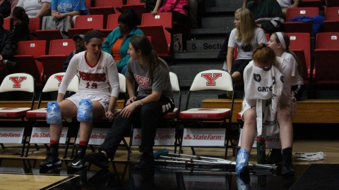 Youngstown State University's Kelsea Newman (far left) and Kelley Wright (right) sit with Nikki Arbanas after leaving the game with injuries.