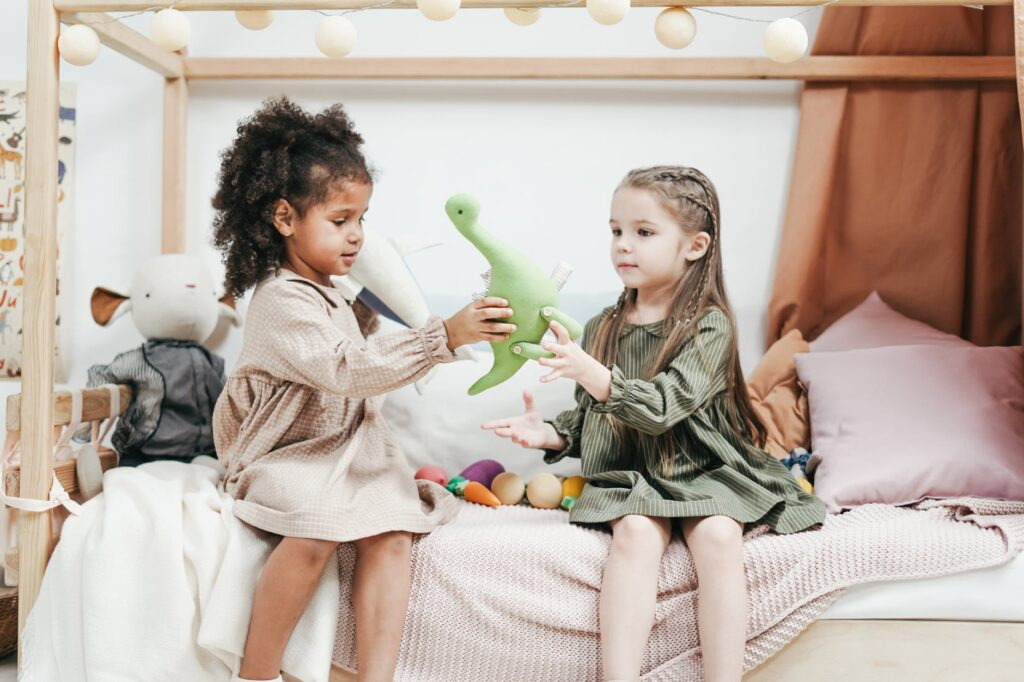 siblings playing a green plush toys