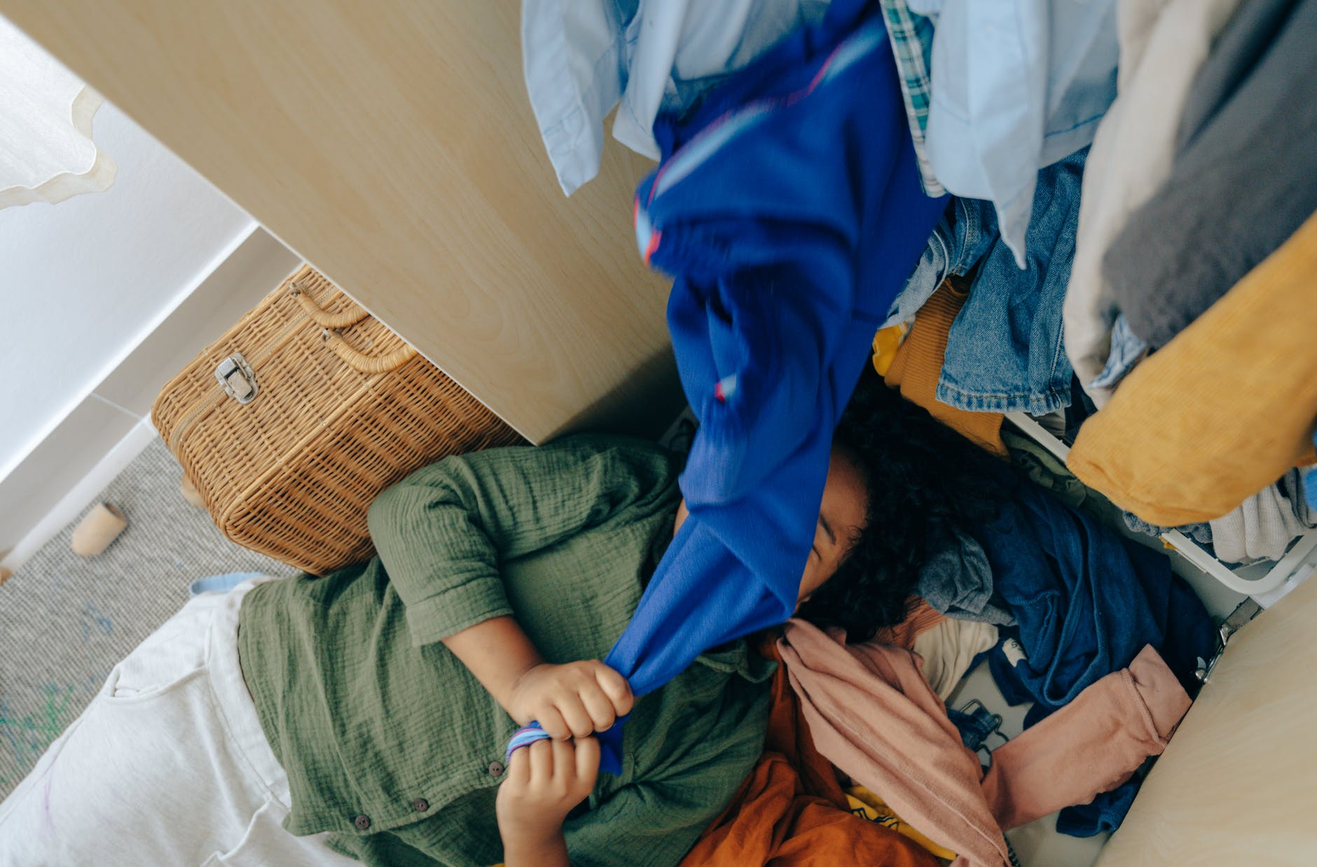 anonymous black girl lying on stack of clothes in bedroom