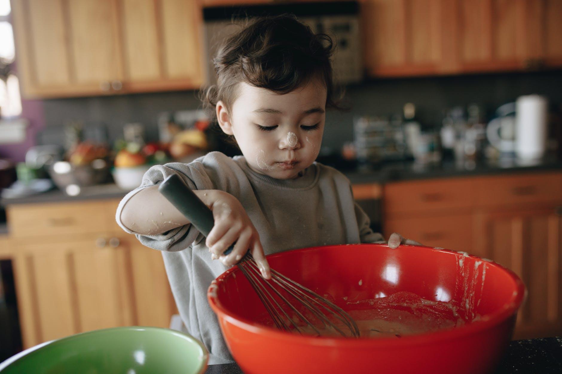 a little child baking in kitchen