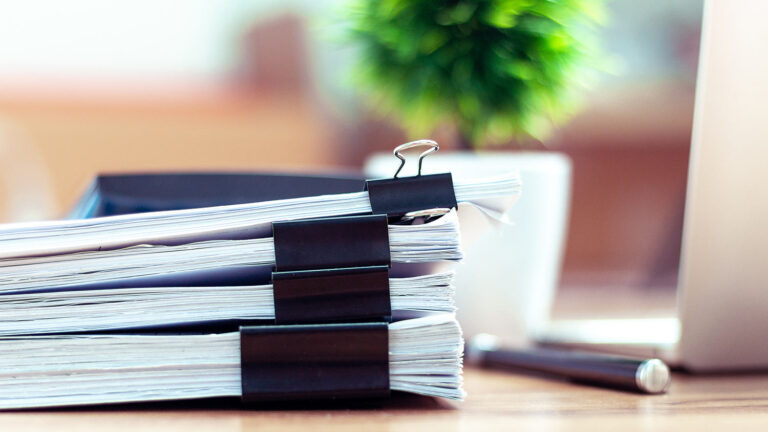Several bundles of papers sitting on top of a desk