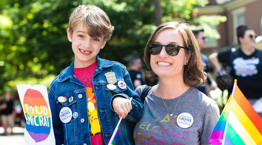 Mother and son smile for portrait during a parade holding a a sign that says Proud Democrat in Bucks County PA