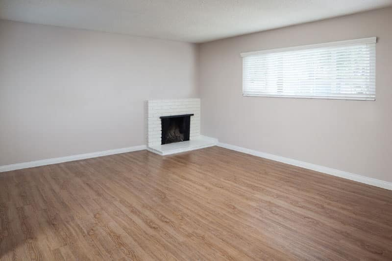 Empty living room with fireplace and wood-style flooring