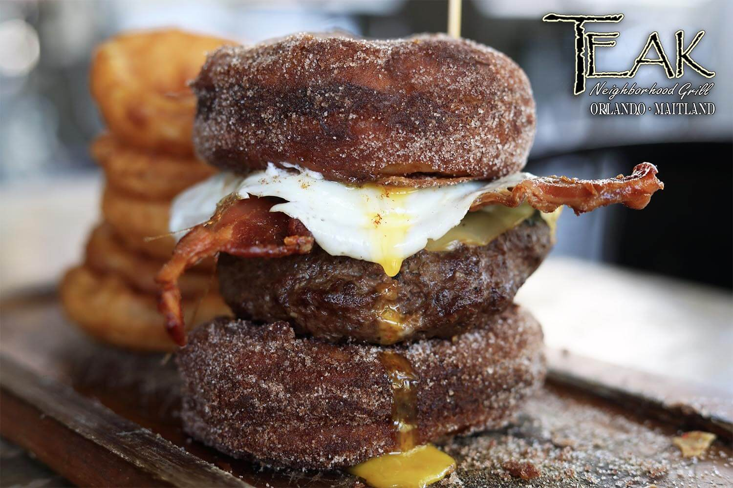 Cronie Burger french doughnuts with half pound angus burger topped with maple-pepper bacon, smoked gouda cheese on an over medium egg
