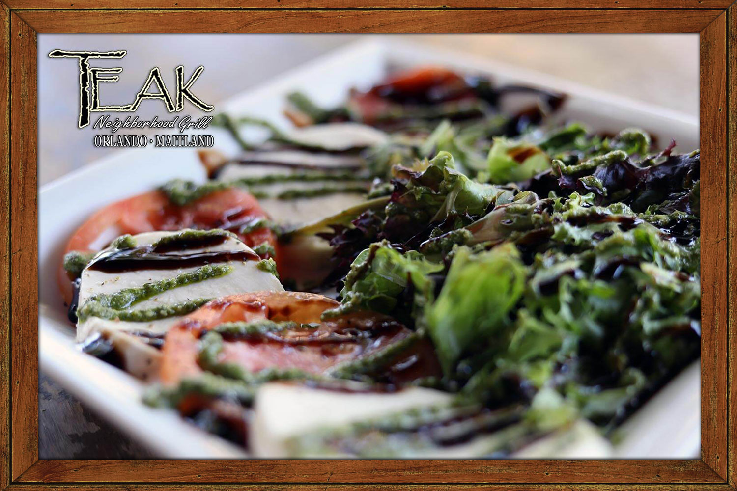 Caprese Salad with fresh tomatoes and mozzarella topped with basil pesto and balsamic glaze