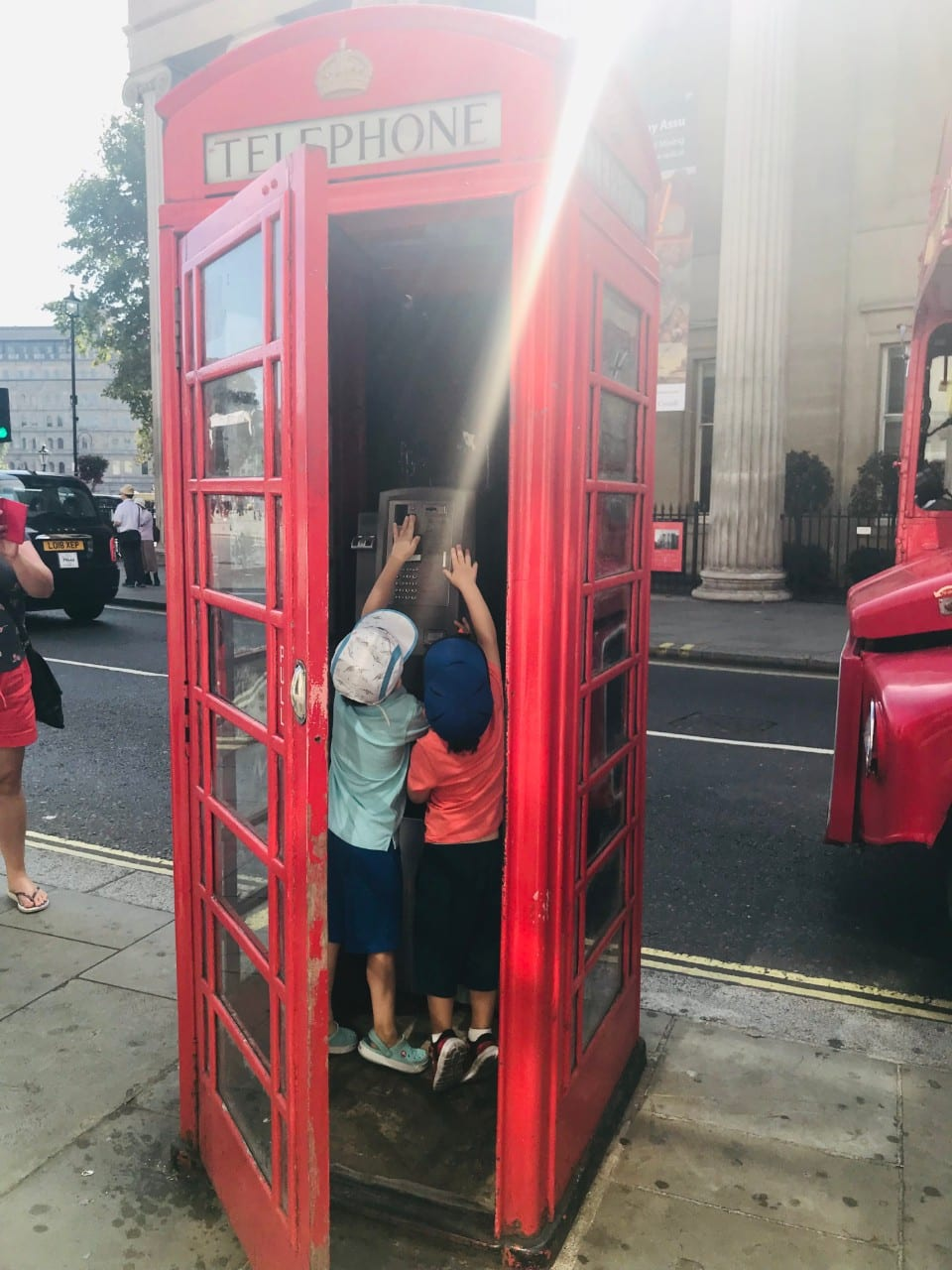 Two boys playing with a phone in a red telephone booth in London, England