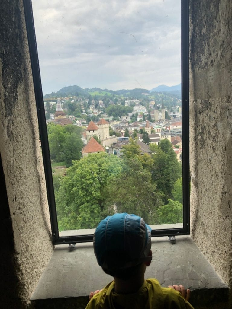 travel tips for traveling to europe with toddlers  - A boy is looking from above at the old town of Lucerne, Switzerland