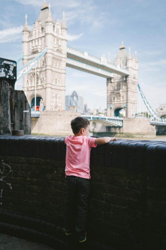 travel tips for traveling to europe with toddlers  - A boy looking at the Tower Bridge in London, England
