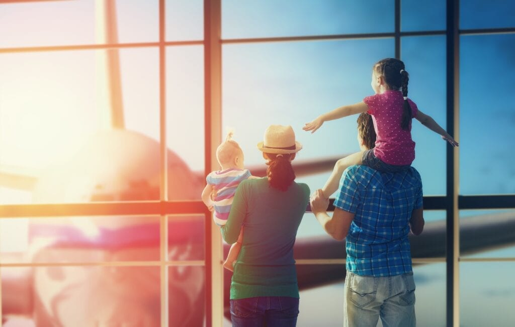 Image of a family at the airport looking at a plane through the window