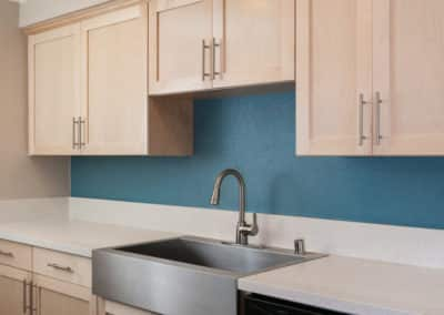 Stainless Steel sink in kitchen with blue walls and light cabinetry