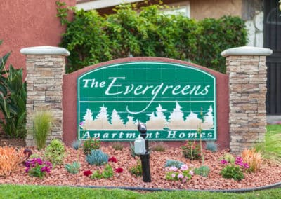 The Evergreens Apartment Homes Sign with plants