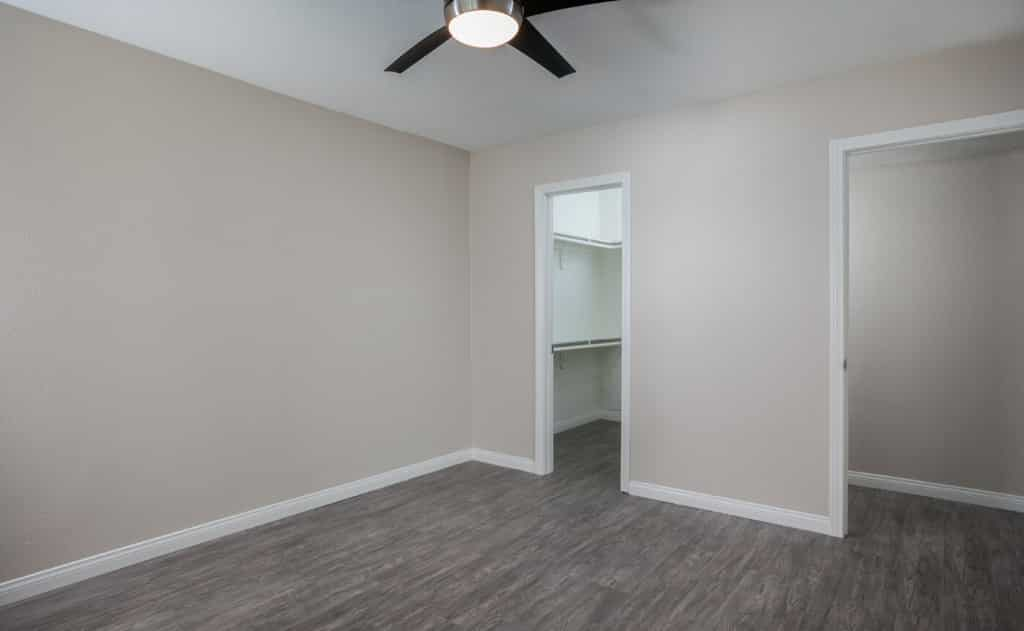 Empty walk-in closet in a bedroom with ceiling fan