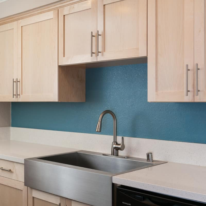 Kitchen with stainless steel sink and light wood cabinets