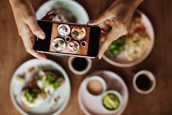 Someone using their phone to take a photo of their food at a restaurant