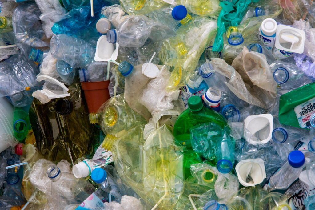 A pile of plastic trash including plastic bags and water bottles.