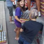 A smiling young girl loads a box filled with soup cans onto a box truck