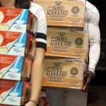 Volunteers carry bulk pudding and cup of noodle soups for unpacking and distribution in Kidz Power Pacs, free food for hungry school aged children
