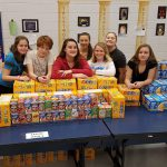 Volunteers stand behind a table stacked with packaged food at a packing event