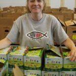 A smiling woman packs applesauce into kidz power pacs