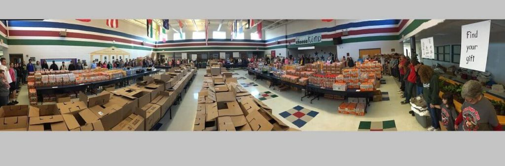 Weekend food for hungry school aged children stacked high on tables in the cafeteria at a Kidz Power Pacs packing event