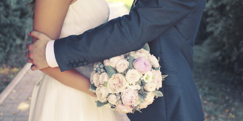 Beautiful sensual wedding couple and gentle bouquet of flowers, groom hugging lovely bride outdoors
