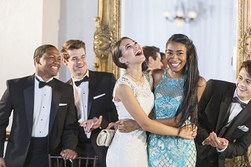 A group of five multi-ethnic teenagers and  young adults dressed in formalwear - dresses and tuxedos attending a party. The two girls are hugging each other as the men applaud.