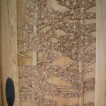 Close up of pine trees carved on Butternut door