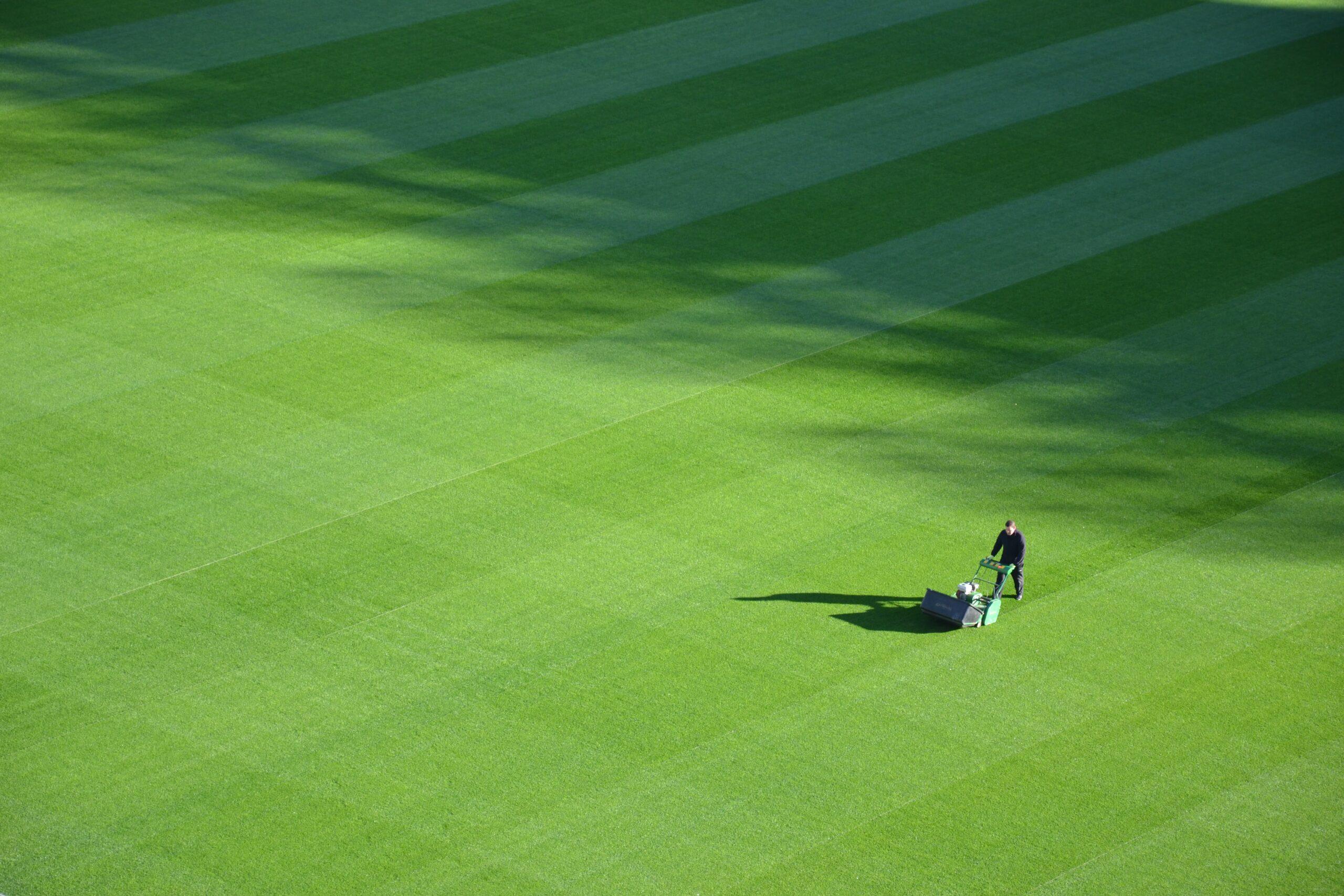 Landscaper mowing a flat, green lawn in a crisscross pattern