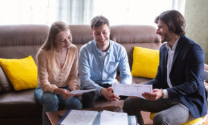 Happy couple with property manager looking at house plan indoors