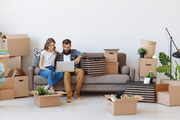 Couple on sofa surrounded by moving boxes