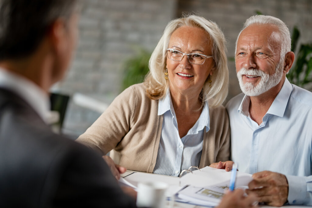 Insurance agent guide to the 2021 insurance enrollment period Happy mature couple talking to their real estate agent while going through paperwork on a meeting in the office.