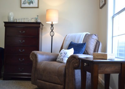 Lamp, Comfortable Chair, and Dresser with Side Table