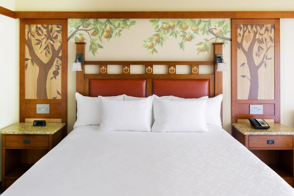 Queen bed with orange trees painted on back wall at Disney's Grand Californian Hotel
