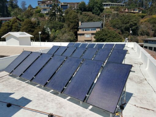 Photo of an array of flat plate solar water heater collectors on a flat roof of a multifamily commercial building