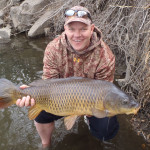 Chris Galvin holds 21 pound common carp with surprised smile.