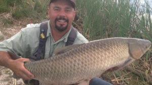 Mike Medina holding a 30 pound Colorado grass carp with a big smile.