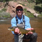 Man on one knee holding spotted brown trout with South Platte River in background