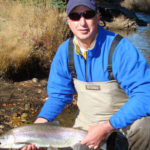 Man on knee holds large and healthy rainbow trout alongside idyllic river