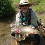 A rainbow trout is held streamside by a Denver fly fishing angler with a goatee and western hat
