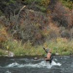 Competitive angler Chris Galvin fighting a fish in heavy river current