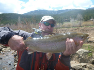 Fly fishing angler holding enormous rainbow trout while holding fly rod in mouth