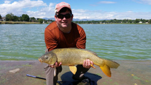 Smiling angler holding carp caught fly fishing in a lake, with mountains in the background.