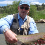 Angler holding a large rainbow trout with sunny mountains behind