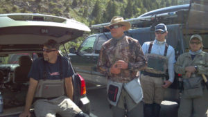 Several anglers in waders standing by their fishing vehicles