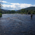 Solo fisherman wading in shallow river with sunny mountains as a backdrop